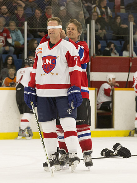 Rocker Jim Cuddy blindfolds NHL great Gary Roberts during the skills competition at the 2015 JUNO Cup. (Photo: CARAS)