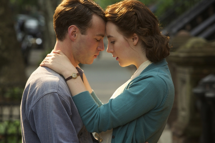 """Mory Cohen as """"Tony"""" and Saoirse Ronan as """"Eilis Lacey"""" in BROOKLYN, which Michael Brook scored. (Photo: Kerry Brown)"""