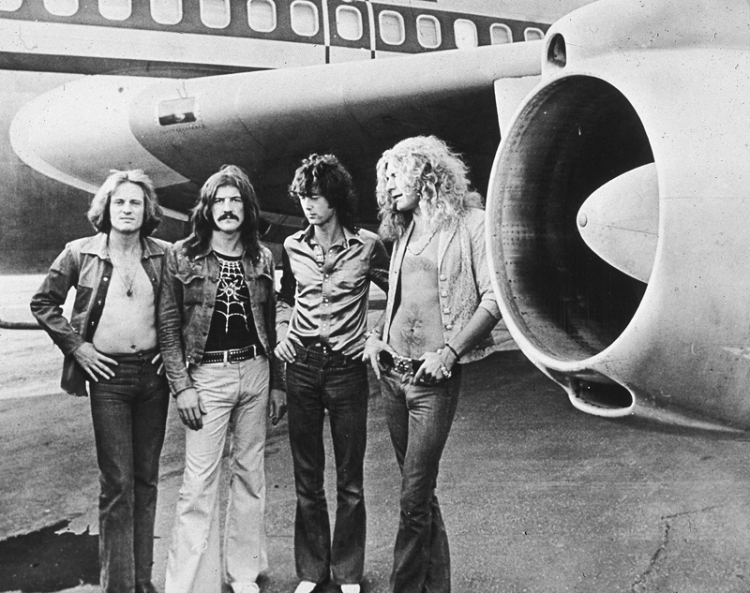 Led Zeppelin, (left - right): John Paul Jones, John Bonham, Jimmy Page and Robert Plant, pose in front of an their private airliner The Starship, 1973. (Photo: Hulton Archive/Getty Images)