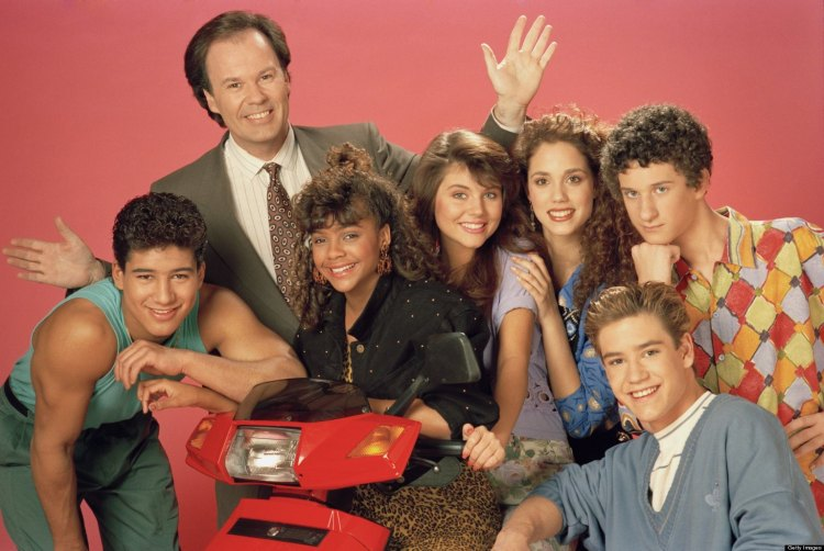 The cast of Saved By The Bell season 2. (Pictured: (L-R) Mario Lopez as Alabert Clifford 'A.C.' Slater, Dennis Haskins as Mr. Richard Belding, Lark Voorhies as Lisa Turtle, Tiffani Thiessen as Kelly Kapowski, Elizabeth Berkley as Jessie Spano, Mark-Paul Gosselaar as Zachary 'Zach' Morris, Dustin Diamond as Screech Powers. (Photo: NBCU Photo Bank)